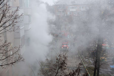 Smoke during a fire in a multi-storey building. A fire truck and firemen arrived to eliminate the dangerous fire