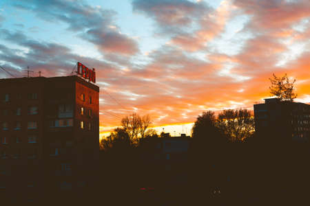 Silhouette of a street and a multi-storey brick building with the inscription in Russian Hero on the background Beautiful urban sunset with clouds.