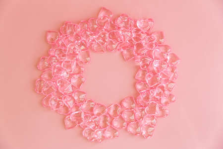 Circle made of pink plastic hearts on a pink background.