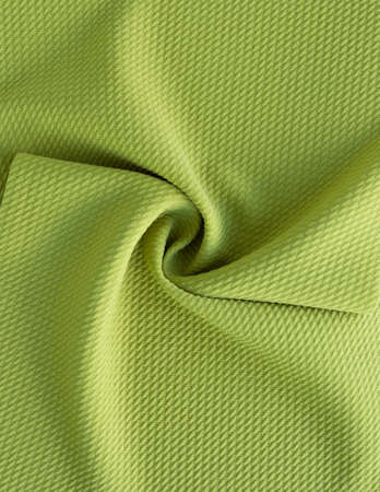Dense light green fabric coiled texture.