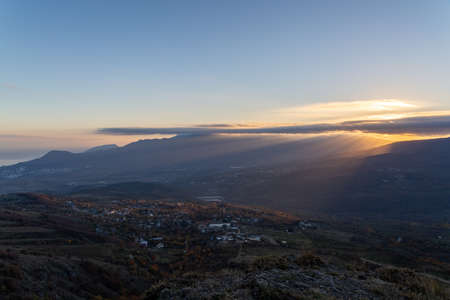 The rays of the setting sun illuminate the mountain valley from under blue clouds