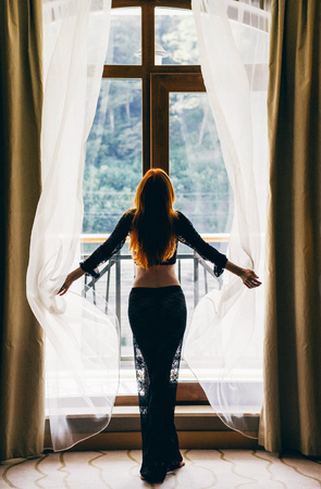 Beautiful young red-haired woman with sexy black clothes opening curtains in her bedroom in Morning. Girl standing near window in the wall. Harmonious morning theme
