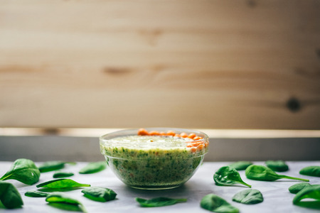 argousier: green smoothie with sea buckthorn, Chia seeds and sesame seeds on a white table, around the spinach leaves. Wooden background. The concept of healthy eating, vegetarian and vegan food Banque d'images