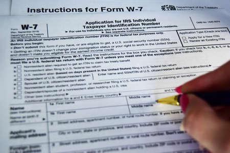 W7 tax form for American citizens, filling out a declaration and instruction. selective focus close-up.