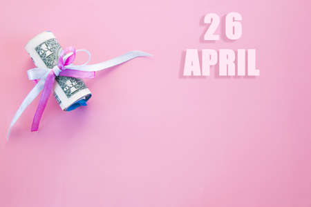 calendar date on pink background with rolled up dollar bills pinned by pink and blue ribbon with copy space. April 26 is the twenty-sixth day of the month.