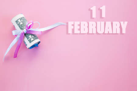 calendar date on pink background with rolled up dollar bills pinned by pink and blue ribbon with copy space. February 11 is the eleventh day of the month.