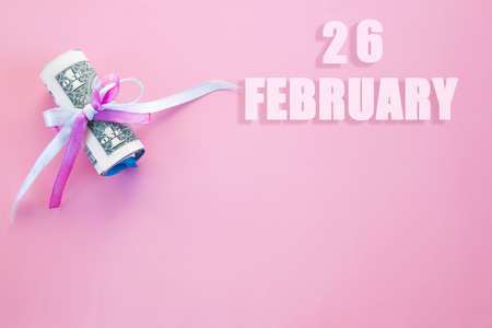 calendar date on pink background with rolled up dollar bills pinned by pink and blue ribbon with copy space. February 26 is the twenty-sixth day of the month.
