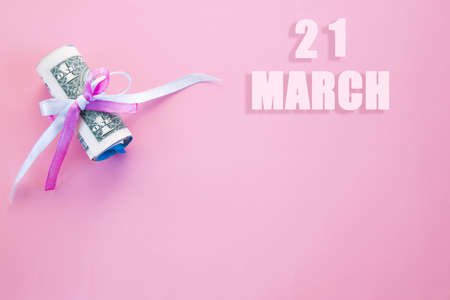 calendar date on pink background with rolled up dollar bills pinned by pink and blue ribbon with copy space. March 21 is the twenty first day of the month.
