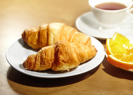 vitamine: Backround continental breakfast with gold french croissants, fruits and cup of tea on wooden table. Great choice on morning. Tasty bread, vitamine orange and invigorating drink