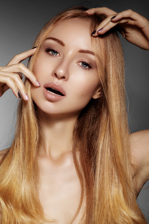 blondy: Beautiful young woman with clean skin, beautiful straight shiny hair, fashion makeup. Glamour make-up, perfect shape eyebrows. Portrait sexy blondy. Beautiful smooth hairstyle Stock Photo