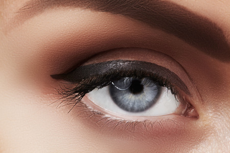 naturel: Close-up macro of beautiful female eye with perfect shape eyebrows. Clean skin, fashion naturel make-up. Good vision. Classic fashion eye liner makeup. Black eyeliner and brown eyeshadows