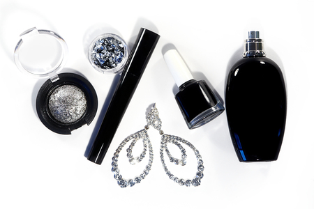 decorative accessories: Collection with cosmetics tools. Fashion evening decorative set with make-up accessories, black nail polish, silver eyeshadows, mascara, luxury perfume and brilliants earrings. Cosmetic & makeup