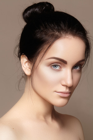 naturel: Beautiful young woman with clean face, shiny skin, fashion natural make-up, perfection eyebrows. Cute bun hairstyle. Spa portrait, naturel cosmetics, healthy fresh look Stock Photo