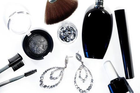accessories: Collection with cosmetics tools. Fashion evening decorative set with make-up accessories, black nail polish, silver eyeshadows, mascara, luxury perfume and brilliants earrings. Cosmetic & makeup