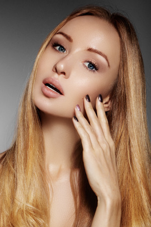 blondy: Beautiful young woman with clean skin, beautiful straight shiny hair, fashion makeup. Glamour make-up, perfect shape eyebrows. Portrait sexy blondy. Beautiful smooth hairstyle. Shiny nail polish