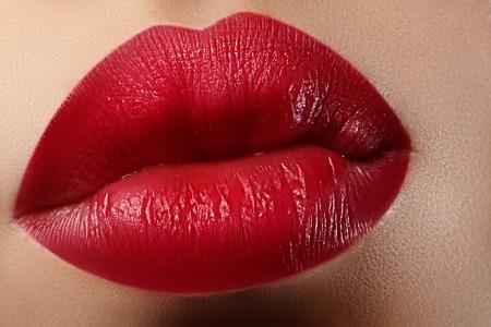 Primer plano de los labios de la mujer con la moda maquillaje rojo. boca femenina hermosa, labios gruesos con maquillaje perfecto. semblante clásico. Parte de la cara femenina. Macro foto de la hermosa compone en los labios llenos.