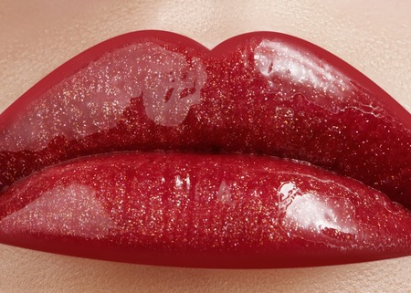 Close-up of female lips with bright makeup. Macro of womans face. Fashion lip make-up with red gloss.Red lipgloss makeup on full female lips