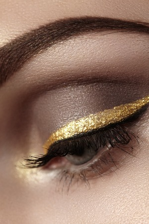 ceremonial make up: Beautiful macro shot of female eye with ceremonial makeup. Perfect shape of eyebrows, eyeliner and pretty gold line on eyelid. Cosmetics and make-up. Closeup macro shot of fashion sparcle visage
