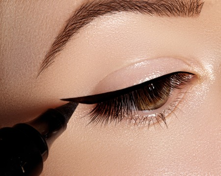 Mujer de moda aplicar delineador de ojos, sombra de ojos, rimel en el párpado, pestañas y cejas con pincel de maquillaje, forma negro línea. Maquillador profesional. Closeup macro belleza foto Foto de archivo