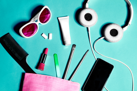 Above view of woman bag stuff . Set of female cosmetics and accessories. Glamour tools and beauty objects. Pink bag, white headphones, sunglasses and smartphone Stock Photo