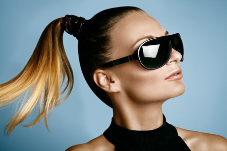 Beautiful young woman with black fashion sunglasses and glamour ponytail hairstyle on blue background. Trendy look for lady. Eye wear style.