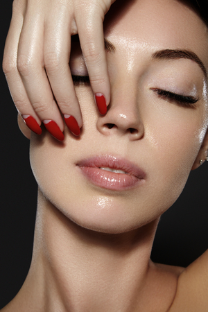 Luxury woman style vamp. Cosmetics, manicure on nails with bright red polish. Dark red lips make-up and nail color. Beauty close-up portrait of female model with red lipstick and clean skin Stock Photo