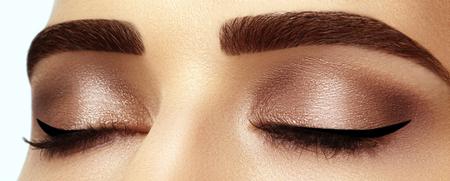 Hermosa macro foto de ojo femenino con maquillaje ahumado clásico. Forma perfecta de cejas, sombras de ojos marrones y pestañas largas. Cosméticos y maquillaje. Closeup macro foto de rostro de ojos ahumados de moda Foto de archivo - 76334199