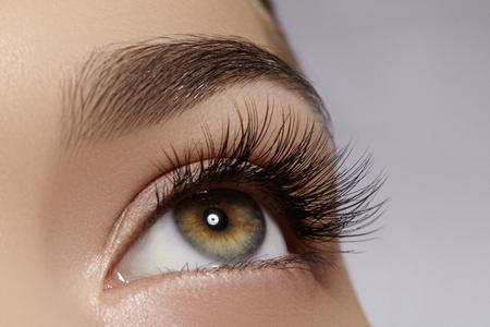 Schönes Makro Schuss von weiblichen Auge mit extrem lange Wimpern und schwarzen Linien Make-up. Perfekte Form Make-up und lange Wimpern. Kosmetik und Make-up. Nahaufnahme Makroaufnahme Mode Augen Gesicht