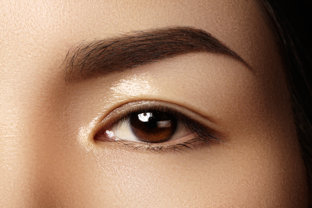 Beautiful female eye with clean skin, daily fashion makeup. Asian model face. Perfect shape of eyebrow. Wet gel for care skin Stock Photo