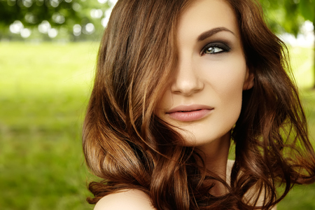 Beautiful woman with fashion makeup, volume hair style on green background summer nature. Sexy hairstyle, clean shiny skin