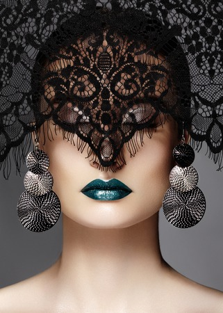 Luxury Woman with Celebrate Fashion Makeup, silver Earrings, black dramatic Lace veil. Halloween sexy witch look or luxe Christmas style. Green metallic Lips Make-up