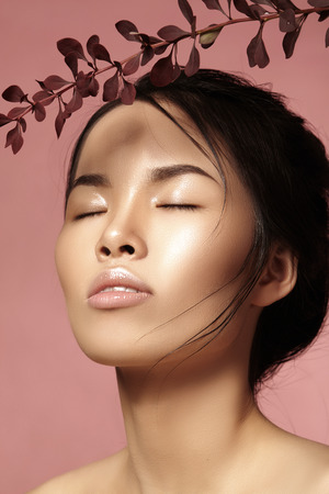 sexy asian woman: Beautiful asian woman with fresh daily makeup. Vietnamese beauty girl in spa treatment with green leafs near face. Pink background