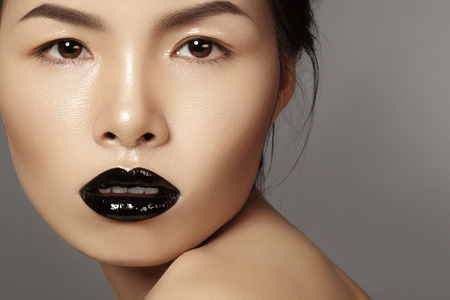 sexy asian woman: Perfect asian model with fashion make-up with dark lipstick and gloss. Beauty halloween style with black lips makeup. Catwalk visage Stock Photo