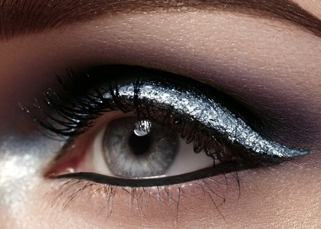 ceremonial make up: Beautiful macro shot of female eye with ceremonial makeup. Perfect shape of eyebrows, eyeliner and pretty silver line on eyelid. Cosmetics and make-up. Closeup macro shot of fashion sparcle visage