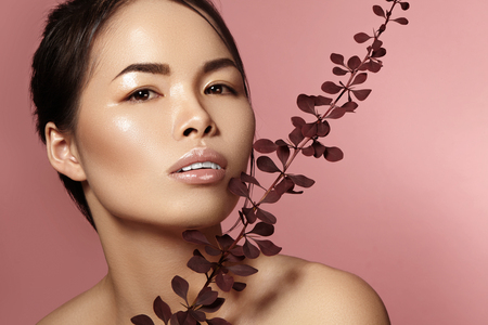Beautiful asian woman with fresh daily makeup. Vietnamese beauty girl in spa treatment with green leafs near face. Pink background
