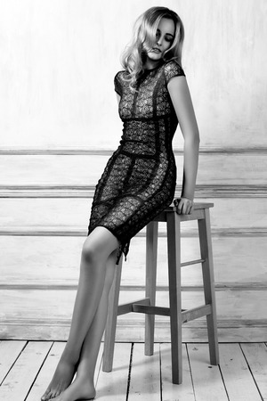 Elegant fashionable woman in black dress. Evening style. Beautiful volume curly hairstyle. Shiny hair. Perfect sexy body.