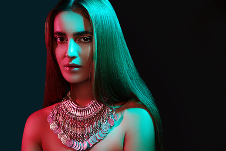 Beautiful woman in a necklace. Model in jewelry from silver. Beautiful indian jewellery. Bright lights photo effect