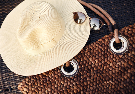 Holiday, Vocation, Travel, Lifestyle and Relax concept. Beach Hat, Boho Bag and Summer Sun Glasses. Brown Sunglass Accessories on wood