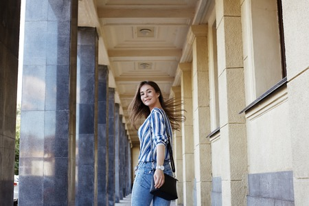 Street Style Outdoors Portrait of Beautiful Girl. Young Woman Smiling. She wearing Print Shirt, Blue Jeans and Black Bag. Happy Lifestyle shoot