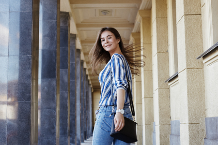 Happy Woman. Street Style Outdoors Portrait of Beautiful Girl. Young Woman Smiling. She wearing Print Shirt, Blue Jeans and Black Bag. Happy Lifestyle shoot