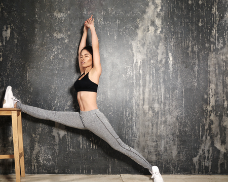 Beautiful young asian Woman Working Out, doing Pilates Exercise in Sportswear. Splits with Yoga Asana, Stretching. Healthy lifestyle, perfect shapes