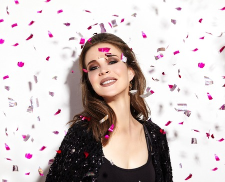 Party Time. Beautiful Happy Woman Smiling. Christmas Style in Confetti. Shiny Celebrate Look with Bright Fashion Make-up. Sexy Evening Makeup 写真素材