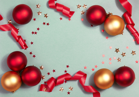 Beautiful Christmas Background with Shiny Red Balls, Glitter Stars and Ribbon in Bright Color. Top view with Copy Space.