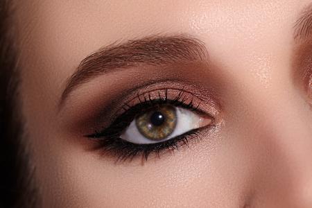 Bella ripresa macro dell'occhio femminile con il classico trucco eyeliner. Forma perfetta di sopracciglia, ombretti marroni e ciglia lunghe. Cosmetici e make up. Colpo a macroistruzione del primo piano del viso degli occhi della fodera di moda