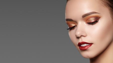 Piękna kobieta z profesjonalnym makijażem. Stylowy makijaż oczu, idealne brwi, błyszcząca skóra. Jasny wygląd mody.