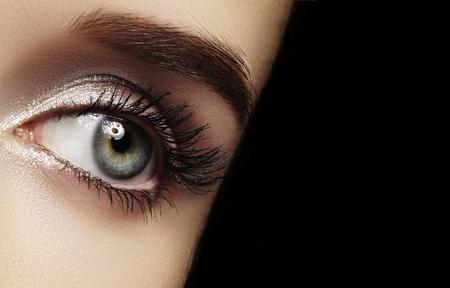 Beautiful Macro Female Eye with Extreme Long Eyelashes and Celebrate Makeup. Perfect Shape Make-up, Fashion Long Lashes. Cosmetics and make-up. Closeup macro shot of fashion eyes visage Imagens