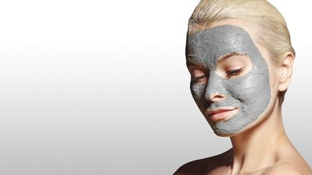 Beautiful Woman Applying White Facial Mask. Beauty Treatments. Close-up Portrait of Spa Girl Apply Clay Facial mask on grey background. 写真素材