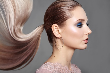 Beautiful Girl with Ponytail Hairstyle. Blond Shiny Straight Hair, Fashion Makeup on Model Face. Woman with Healthy Skin and Party Glitter Make-up 写真素材