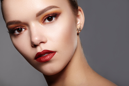 Beautiful Woman with Professional Makeup. Party Gold Eye Make-up, Perfect Eyebrows, Shine Skin. Bright Fashion Look with Red Lips