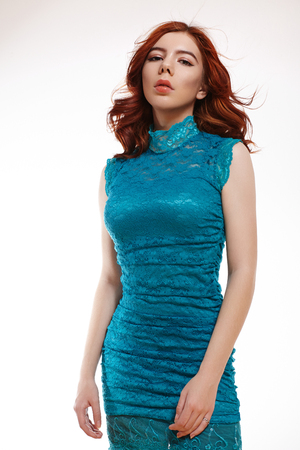 Romantic European Girl with Shiny Ginger Hair. Cute Tender Teenager Girl with Curly Red Hair in Blue Lacy Dress on White Background 写真素材